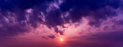 Panorama background of the sun in twilight purple sky and clouds. The sun in twilight purple sky and clouds damatic panorama background Royalty Free Stock Photos