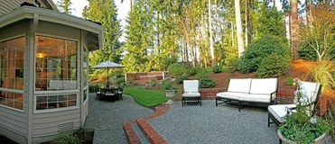 Panorama of backyard. With patio set, chairs, and jacuzzi Royalty Free Stock Image