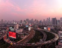 Panorama of Bangkok at dusk with skyscrapers in background & heavy traffic on elevated expressways & circular interchanges Stock Image