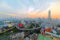 Panorama of Bangkok at dusk with skyscrapers in background and traffic trails on elevated expressways and circular interchanges Stock Photo