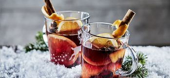 Panorama banner with Christmas Gluhwein. Panorama banner with two glasses of Christmas Gluhwein or mulled red wine garnished with stick cinnamon and served on Stock Photography