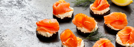 Panorama banner of fresh smoked salmon canapes. With dill on a dark textured background with copy space Stock Photo