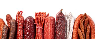 Panorama of traditional spicy dried sausages. Panorama banner or header of an assortment of traditional spicy dried beef and pork sausages arranged in a neat Royalty Free Stock Image