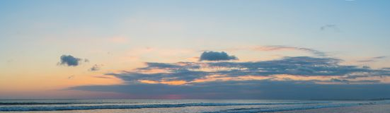 Panorama, Banner, long format of Sunset on the Kuta beach with reflection in the water on the island of Bali.  stock photo