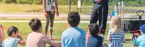 Panorama- barn för bakre sikt för närbild mångkulturella på gräsäng av den utomhus- leken royaltyfria foton
