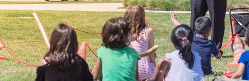 Panorama- barn för bakre sikt för närbild mångkulturella på gräsäng av den utomhus- leken royaltyfri bild