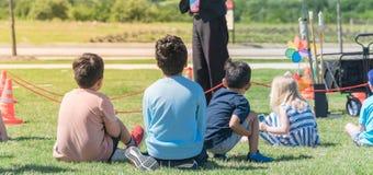 Panorama- barn för bakre sikt för närbild mångkulturella på gräsäng av den utomhus- leken arkivfoton