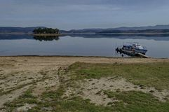 Panorama of Batak dam reservoir with island and passenger-ship in the water, coastal autumn glade, forest, hill royalty free stock photo