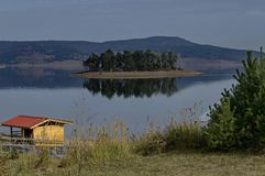 Panorama of Batak dam reservoir with island in the water and coastal autumn glade, cottage, forest, hill at Rhodope mountains royalty free stock photo
