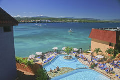 Panorama of the Bay at Sosua, Dominican Republic. A resort, curved, swimming pool graces the foreground against the blue water of the Caribbean Sea; white Royalty Free Stock Image