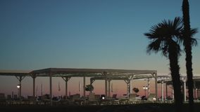 Panorama of beach infrastructure with palm trees at sunset light. Wide shot stock footage