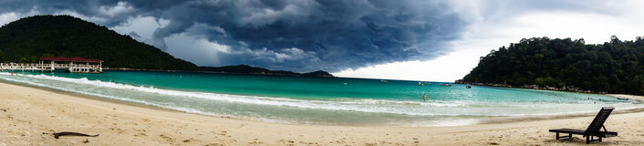 Panorama of the beach with a lonely standing chaise longue again. St the background of approaching thunderstorms Storm clouds. Pulau Pertianian, Malaysia Stock Photos