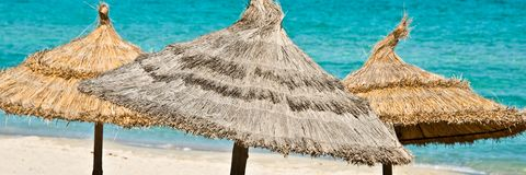 Panorama of beach umbrellas, blue sea bacground stock images
