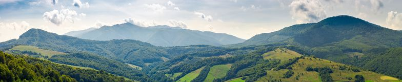 Panorama of beautiful Carpathian mountains. Perfect countryside landscape. rural field on the nearest forested hills. Mighty Borzhava ridge in the distance Royalty Free Stock Photo