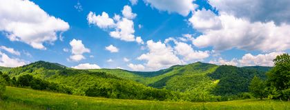 Panorama of beautiful countryside in summer. Beautiful landscape with forested mountains and grassy field under the blue sky with some clouds Royalty Free Stock Images