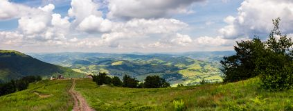 Panorama of beautiful landscape in mountains. Gorgeous view from Borzhava mountain ridge. road down the grassy hill to tourist base. wonderful summer weather Stock Photos