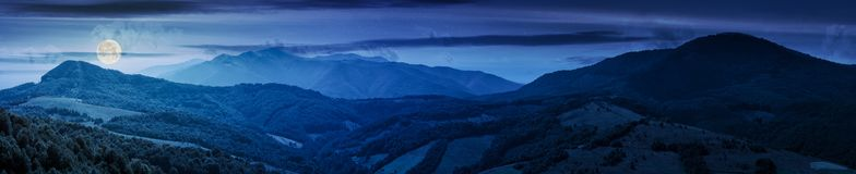 Panorama of beautiful mountain ridge at night. In full moon light. perfect countryside landscape. rural field on the nearest forested hills. Mighty Borzhava Royalty Free Stock Image