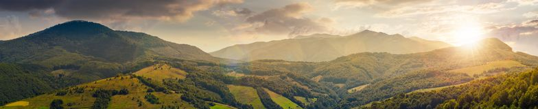 Panorama of beautiful mountain ridge at sunset. In evening light. perfect countryside landscape. rural field on the nearest forested hills. Mighty Borzhava royalty free stock photos