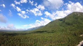 Panorama of beautiful mountains with green forest, blue sky and white clouds stock video footage