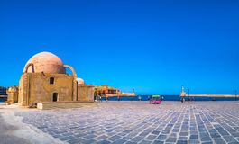 Panorama of the beautiful old harbor of Chania with the amazing lighthouse, mosque, venetian shipyards, at sunset, Crete. royalty free stock photography