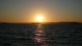 Panorama of beautiful sunset by the sea. Military ships at sea at sunset