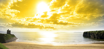 Panorama of a Beautiful yellow sun over the Ballybunion beach. And castle in Ireland one summers day Stock Photo