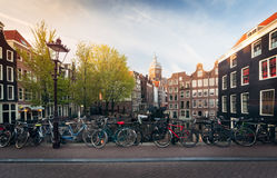 Panorama of beautifull Amsterdam bridge with bicycles, Holland. Panorama of beautifull Amsterdam bridge with bicycles and typical dutch houses at sunset, Holland Stock Photos