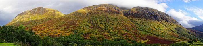 Panorama of Ben Nevis Range. A panorama of the Ben Nevis range from Glen Nevis showing autumnal colours. Ben Nevis (to left) is the highest mountain in the stock photo