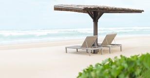 Två tomma chaiselongues under skjul på strand. Arkivfoto