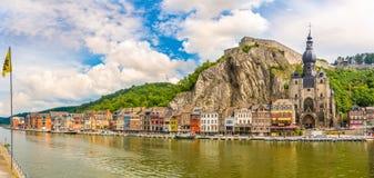 Panorama bij enbankment van Meuse rivier met huizen en kerk van Onze Dame in Dinant - België stock foto's