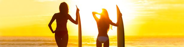Panorama-Bikini-Surfer-Frauen-Mädchen-Surfbrett-Sonnenuntergang-Strand stockfoto
