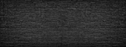 Panorama of black brick wall for site caps as background. Black brick wall, brickwork background for design Royalty Free Stock Photo