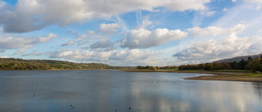 Panorama of Blagdon Lake, Somerset, UK. Resevoir at the edge of the Mendip Hills in England, with flock of birds under blue sky with clouds Stock Image