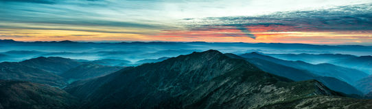 Panorama with blue mountains and hills at sunset Royalty Free Stock Images