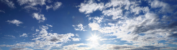Panorama of blue sky with sun and clouds Stock Images