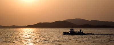 Panorama of a boat at sunset. A panoramic image of a small fishing boat at sunset off the coast of Inchon, Korea Stock Photos