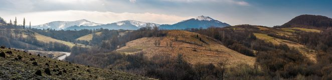 Panorama of Borzhava mountain ridge in springtime. Beautiful countryside with snowy tops and forested hills. location Volovets, Ukraine Royalty Free Stock Photo
