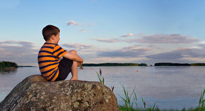 Panorama of a boy sitting on rock in summer evening sunlight Royalty Free Stock Images