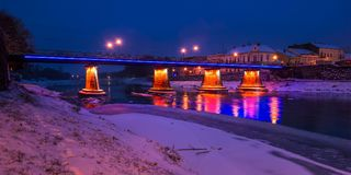 Panorama of bridge through the river Uzh at night. Beautiful cityscape of old european town Uzhgorod in winter Royalty Free Stock Photo