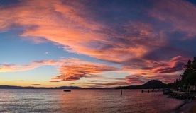 Bright pink, orange and blue sunset with a boat in the middle and a dock on the right corner standing on Lakeside. Panorama of a bright pink, orange and blue royalty free stock photography