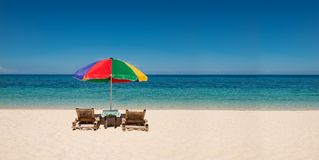 Panorama with bright umbrella and beach chairs with copyspace. Panorama of colorful umbrella with beach chairs on the white sand beach with blue sky,copyspace Royalty Free Stock Images