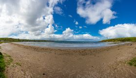 Panorama of Browns Bay. Co. Antrim/N. Ireland - May 31, 2015: A panorama of Browns Bay in N. Ireland on the County Antrim coast on a partly sunny spring day stock image