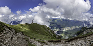 A panorama from Bucegi mountains, Romania, down in the valley where lays tourist cities like Busteni and Sinaia, and on top of a p. The Heroes' Cross, monument Stock Photos