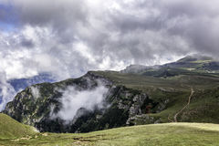 A panorama from Bucegi mountains, Romania, during a summer day, with beautiful clouds. A path through the mountains Royalty Free Stock Photos