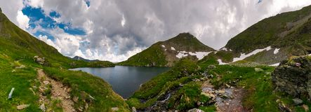 Panorama of Capra lake, Romania. Gorgeous landscape of Fagarasan mountains on a cloudy summer day Royalty Free Stock Photography