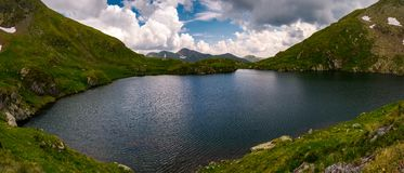 Panorama of Capra lake, Romania. Gorgeous landscape of Fagarasan mountains on a cloudy summer day Royalty Free Stock Image