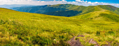 Panorama of Carpathian mountain ridge. Panoramic summer landscape in Carpathians. road through grassy hillside meadow on Borzhava mountain ridge. popular tourist Stock Photo
