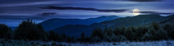 Panorama of Carpathian mountains at night. In full moon light. beautiful landscape with forested hills and Apetska mountain in the distance Royalty Free Stock Photos