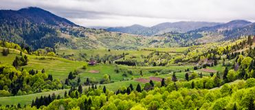 Panorama of Carpathian rural area in springtime. Beautiful mountainous landscape on a cloudy day Royalty Free Stock Image