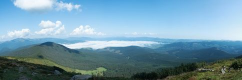 Panorama of Carpathians mountains at summer, west Ukraine. White clouds in blue sky. Low clouds floating between. Mountain ranges. Ukrainian nature panoramic royalty free stock image